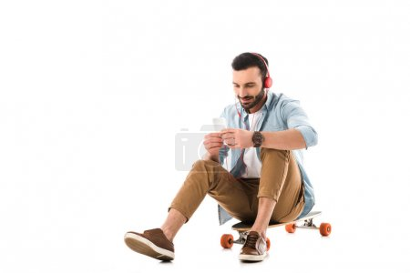 Photo for Handsome smiling man listening music in headphones while sitting on longboard and using smartphone isolated on white - Royalty Free Image
