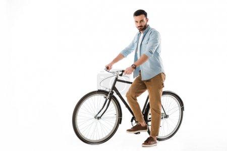 Photo pour Homme barbu sérieux avec le vélo regardant l'appareil-photo isolé sur le blanc - image libre de droit