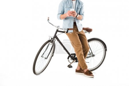 Photo for Partial view of adult man with bicycle using smartphone isolated on white - Royalty Free Image