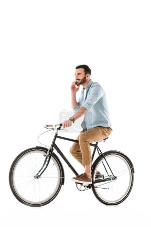 Photo for Smiling bearded man riding bicycle and talking on smartphone isolated on white - Royalty Free Image