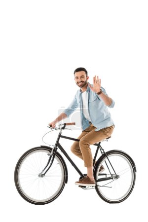 Photo for Handsome cheerful man riding bicycle and showing hello gesture at camera isolated on white - Royalty Free Image