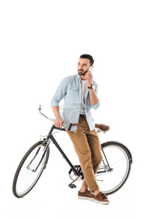 Photo for Thoughtful man with bicycle talking on smartphone and looking away isolated on white - Royalty Free Image