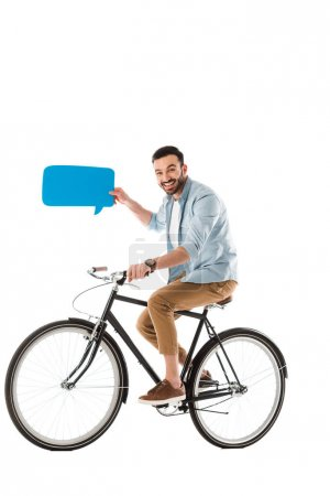 Photo for Smiling handsome man holding speech bubble and riding bicycle isolated on white - Royalty Free Image