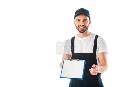 Photo pour Cheerful delivery man holding clipboard with empty paper and looking at camera isolated on white - image libre de droit
