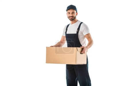 Photo for Handsome delivery man in overalls holding cardboard box and smiling at camera isolated on white - Royalty Free Image