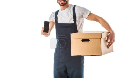 Photo for Cropped view of smiling delivery man with carton box holding smartphone with blank screen isolated on white - Royalty Free Image