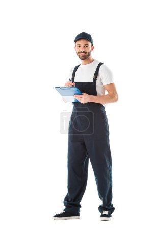 Photo for Smiling delivery man writing on clipboard and looking at camera isolated on white - Royalty Free Image