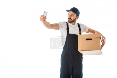 Photo for Handsome delivery man taking selfie with smartphone while holding cardboard box isolated on white - Royalty Free Image