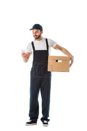 Photo for Smiling delivery man using smartphone while holding cardboard box isolated on white - Royalty Free Image