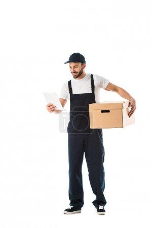Photo pour Courrier gai regardant le papier avec l'ordre tout en retenant la boîte en carton d'isolement sur le blanc - image libre de droit