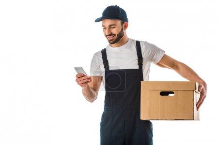 Foto de Alegre guapo repartidor usando el teléfono inteligente mientras sostiene la caja de cartón aislado en blanco - Imagen libre de derechos