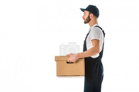 Photo for Side view of delivery man in overalls and cap holding cardboard box isolated on white - Royalty Free Image