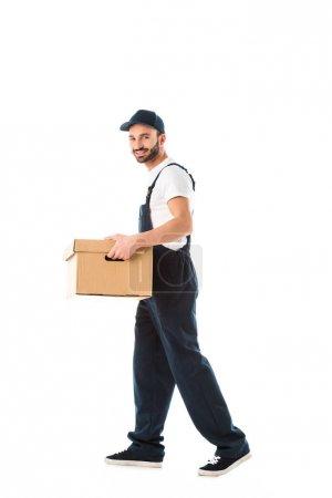 Photo pour Beau livreur de sourire portant la boîte en carton et regardant l'appareil-photo isolé sur le blanc - image libre de droit
