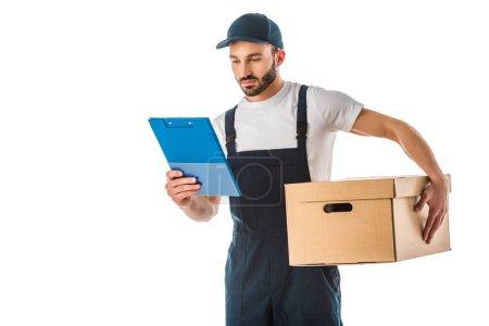 Foto de Atento guapo repartidor sosteniendo caja de cartón y mirando el portapapeles aislado en blanco - Imagen libre de derechos