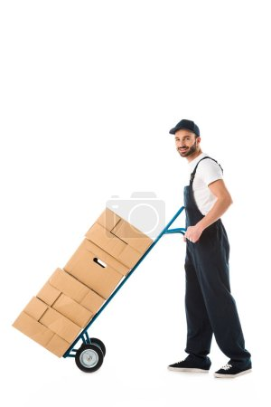 Photo for Smiling delivery man transporting hand truck loaded with carton boxes isolated on white - Royalty Free Image