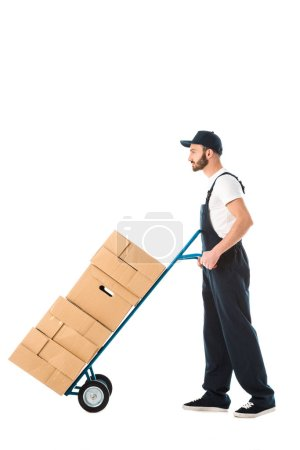 Photo for Serious delivery man transporting hand truck loaded with cardboard boxes isolated on white - Royalty Free Image