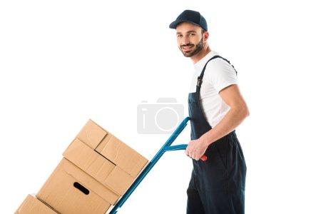 Photo pour Cheerful delivery man transporting hand truck with cardboard boxes and looking at camera isolated on white - image libre de droit