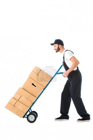 Photo for Side view of delivery man transporting cardboard boxes loaded on hand truck isolated on white - Royalty Free Image
