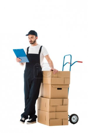 serious delivery man standing near hand truck loaded with cardboard boxes and looking at clipboard isolated on white