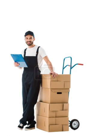 Photo for Cheerful delivery man standing near hand truck loaded with carton boxes and holding clipboard isolated on white - Royalty Free Image