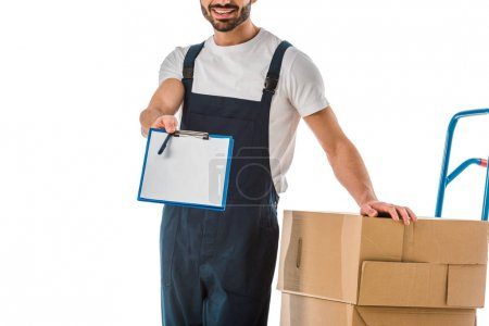 Photo for Cropped view of delivery man standing near cardboard boxes and holding clipboard with blank paper isolated on white - Royalty Free Image