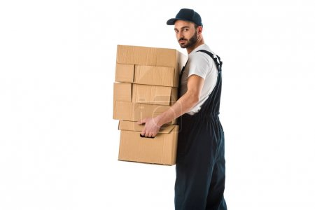 Photo for Serious delivery man carrying cardboard boxes and looking at camera isolated on white - Royalty Free Image