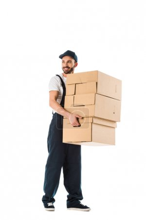 Photo for Smiling delivery man carrying cardboard boxes and looking away isolated on white - Royalty Free Image