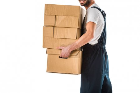 Photo for Partial view of delivery man in overall carrying cardboard boxes isolated on white - Royalty Free Image