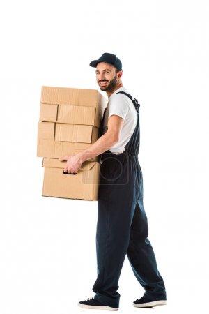 Photo pour Livreur joyeux portant des boîtes en carton et regardant la caméra isolée sur blanc - image libre de droit