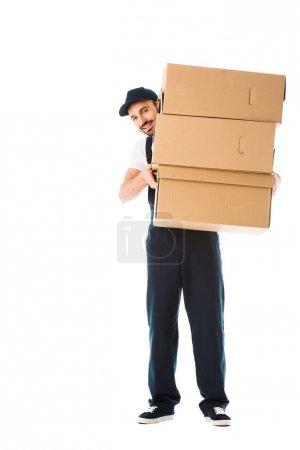 Lächelnder Zusteller mit Pappkartons und Blick in die Kamera isoliert auf weiß