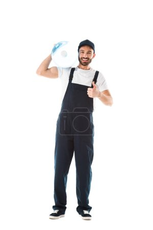 Photo for Cheerful delivery man holding bottle of water and showing thumb up isolated on white - Royalty Free Image