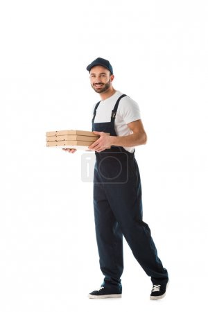 Photo pour Cheerful delivery man carrying pizza boxes and smiling at camera isolated on white - image libre de droit