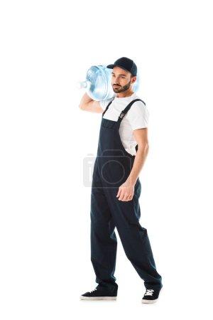 Photo pour Livreur sérieux dans des salopettes portant la bouteille d'eau d'isolement sur le blanc - image libre de droit