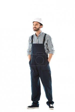Photo pour Beau travailleur de la construction souriant avec les mains dans les poches regardant isolé sur blanc - image libre de droit