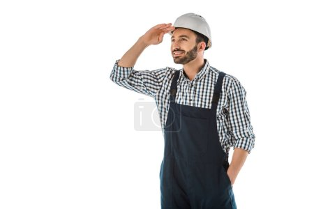 Photo for Happy construction worker in overalls and helmet looking up isolated on white - Royalty Free Image