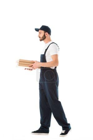 Photo pour Livreur sérieux dans des salopettes portant des boîtes à pizza isolés sur le blanc - image libre de droit