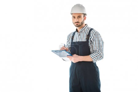 Photo for Serious bearded construction worker writing on clipboard and looking at camera isolated on white - Royalty Free Image