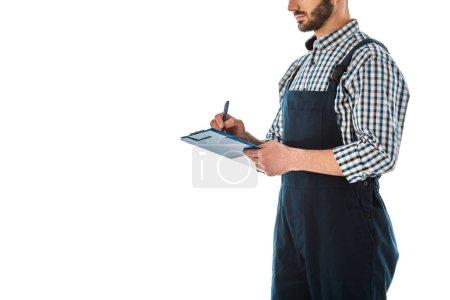 Photo pour Vue partielle de l'ouvrier de construction écrivant sur le presse-papiers isolé sur le blanc - image libre de droit