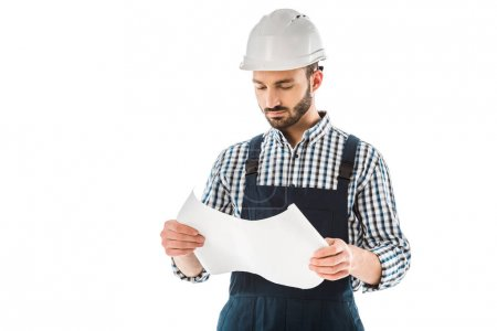 Photo for Concentrated construction worker in helmet looking at building plan isolated on white - Royalty Free Image