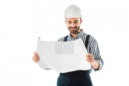 Photo for Smiling construction worker in helmet looking at building plan isolated on white - Royalty Free Image