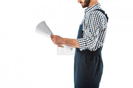 Photo pour Vue recadrée de l'ouvrier de construction dans les salopettes regardant le plan de construction isolé sur le blanc - image libre de droit