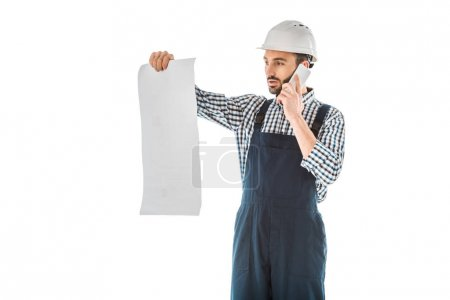 Photo for Attentive construction worker talking on smartphone while looking at building plan isolated on white - Royalty Free Image
