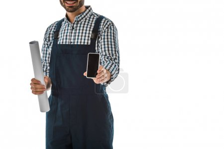 Photo for Partial view of construction worker holding smartphone with blank screen and rolled paper isolated on white - Royalty Free Image