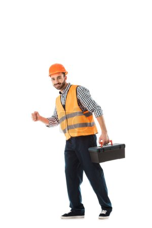 cheerful construction worker in safety vest and helmet holding toolbox isolated on white