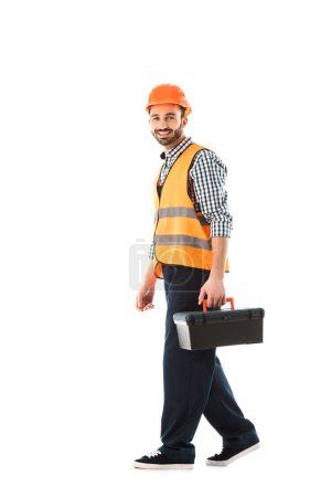 Photo for Smiling construction worker in safety vest and helmet holding toolbox and looking at camera isolated on white - Royalty Free Image