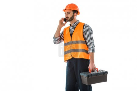 Photo for Attentive construction worker talking on smartphone while holding toolbox and looking away isolated on white - Royalty Free Image