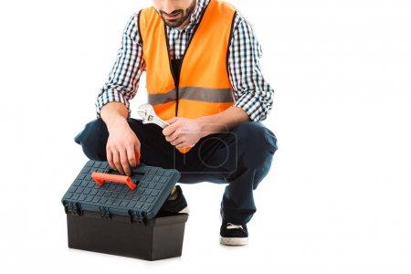 Photo pour Vue partielle du travailleur de construction obtenant la clé réglable hors de boîte à outils d'isolement sur le blanc - image libre de droit