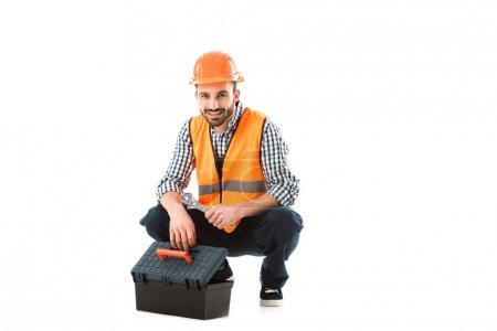 Photo pour Travailleur de la construction gai assis près de la boîte à outils et la tenue de clé réglable isolé sur le blanc - image libre de droit
