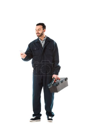 Photo for Cheerful workman in overalls using smartphone and holding toolbox isolated on white - Royalty Free Image