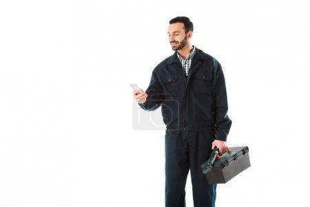Photo pour Ouvrier souriant dans des salopettes utilisant le smartphone tout en retenant la boîte à outils d'isolement sur le blanc - image libre de droit